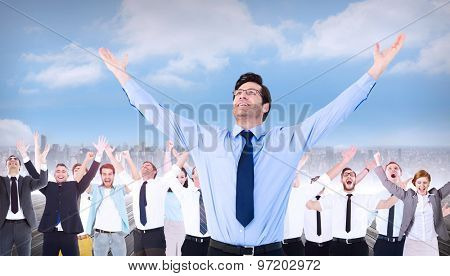 Cheering businessman with his arms raised up against cityscape on the horizon