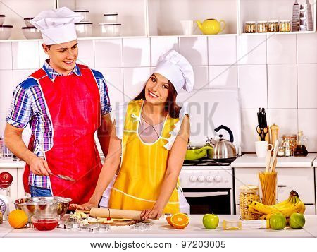 Young happy family cooking at kitchen.