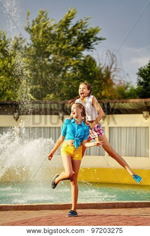Girl Jumping Holding The Shoulders Of Her Best Friend.