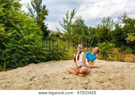 Best Girlfriends Sitting On Sand At Beach.