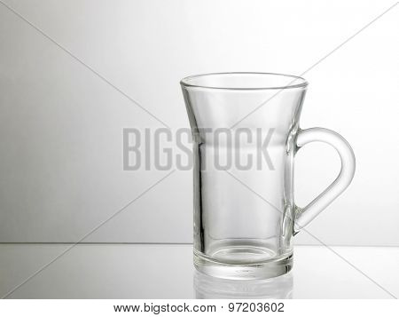 Glass transparent empty mug, with reflection on a white background.