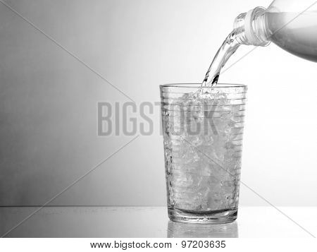 pouring water in Glass with ice isolated on white