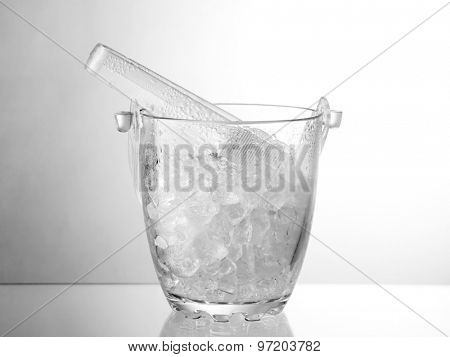 Glass ice bucket isolated on glass table