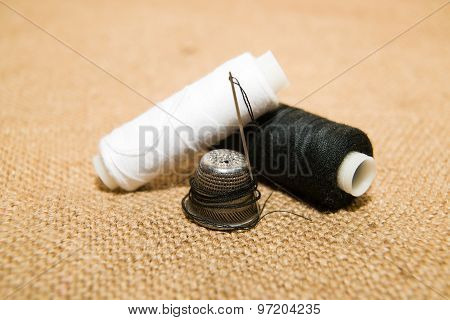 Needle, Thimble And Thread Spool On The Old Cloth
