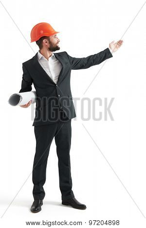 smiley businessman in formal wear and orange helmet pointing his hand at something. isolated on white background