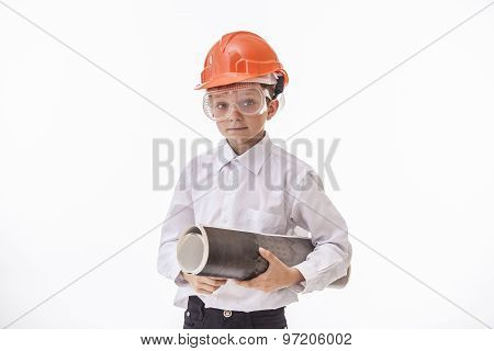 Boy Child In A Protective Helmet And Goggles With A Construction Drawing