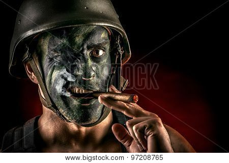 Close-up portrait of a brave soldier in war paint smoking a cigar. Black background. Military, war. Special forces.