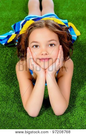 Beautiful smiling girl in bright summer dress lying on a grass.
