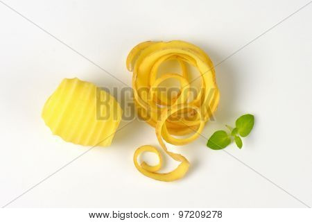 peeled potato and peel spiral on white background