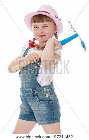 little girl holding a rake