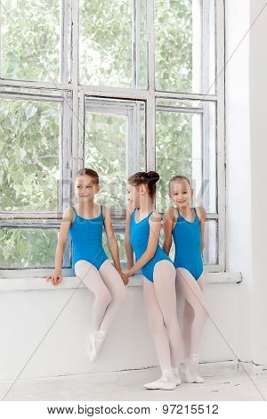 Three little ballet girls standing and talking together