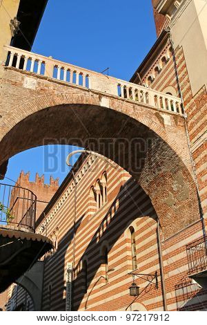 VERONA, ITALY - SEPTEMBER 13, 2014: Arco della Costa, monumental arch with hanging whale's rib on September 13, 2014 in Verona, Italy.The legend says that rib will fall on a just person who walks under it