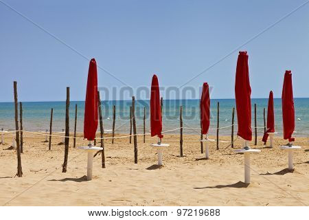 Red closed umbrellas and wooden poles on a sandy Mediterranean beach Sicily on sunny summer day