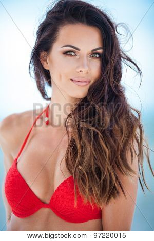 Sexy brunette girl in red swimsuit posing on a beach