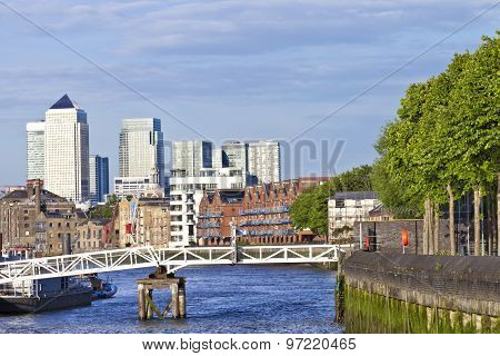 London Canary Wharf Docklands skyline view over Thames river along bankside with green trees and wat