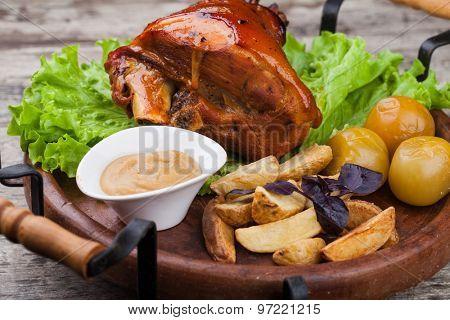 Appetizing roast pork knuckle on cutting board