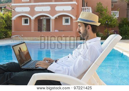 Young Businessman Looking Picture On His Laptop By The Pool While On Vacation