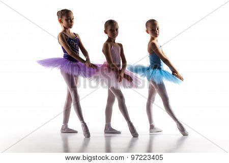Three little ballerinas dancing in dance studio