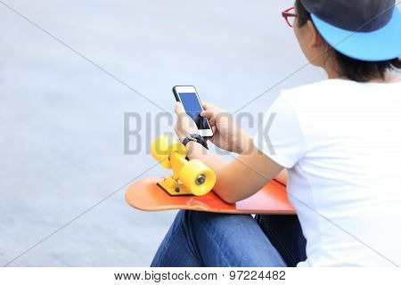 young skateboarder use cellphone sit on city stairs