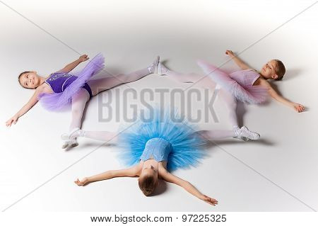 Three little ballet girls in tutu lying and posing together