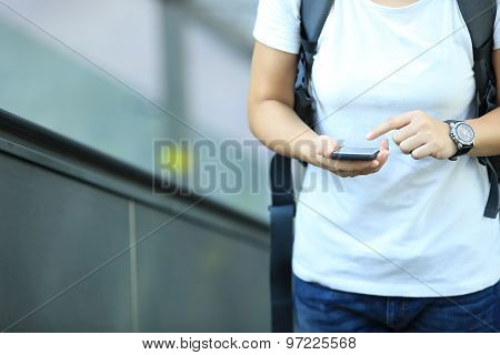 closeup of young woman skateboarder use smart phone in city escalator