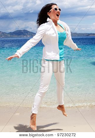 travel concept - happy girl jumping on the beach, summer holiday.