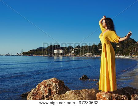 Fashion concept - Woman with long yellow dress walking alone on the beach