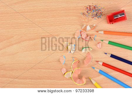 High angle view of six colored pencils on a school desk with a sharpener and shavings. Horizontal with copy space. Back to school concept.