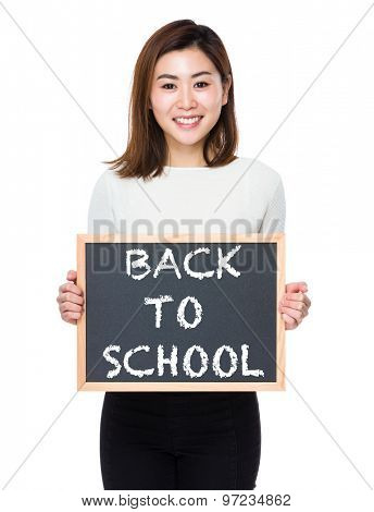 Young woman with the blackboard showing phrase of back to school