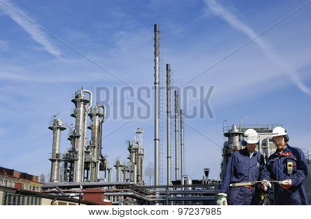 oil and gas workers, engineers, walking in front of refinery industry, wide-angle sharpness.
