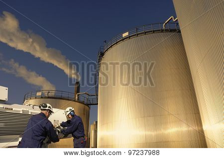 refinery workers with machinery and large fuel-storage tanks, towers, early evening sunset, focal point on workers