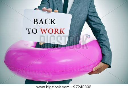 businessman with a pink swim ring shows a signboard with the text back to work written in it