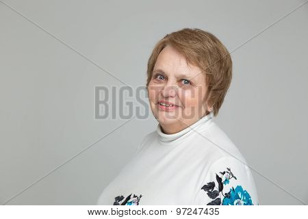 Portrait of a Senior Russian woman in white dress on grey background