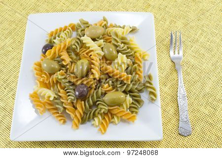 Colored Macaroni With Olives Served On The Yellow Tablecloth With A Fork