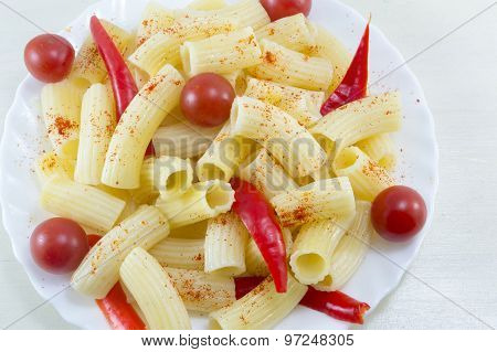 Macaroni With Cherry Tomatoes And Red Pepper Served In A White Plate On  A Wooden Table