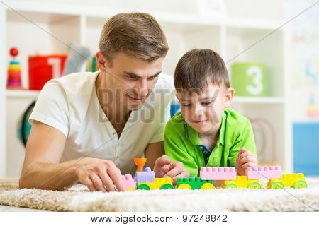 Father and child playing construction game together at home.