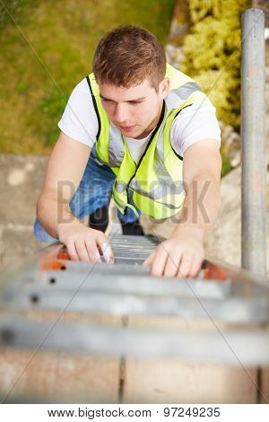 Construction Worker Climbing Ladder On Building Site