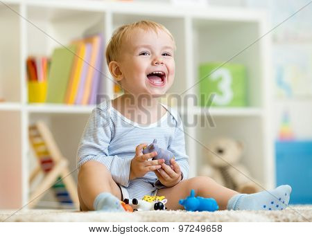 Happy little boy. Smiling child plays animal toys at home or kindergarten.