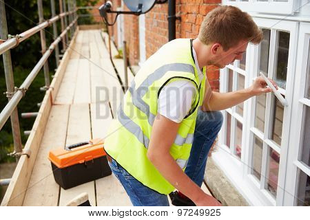 Decorator On Scaffolding Painting Exterior House Windows