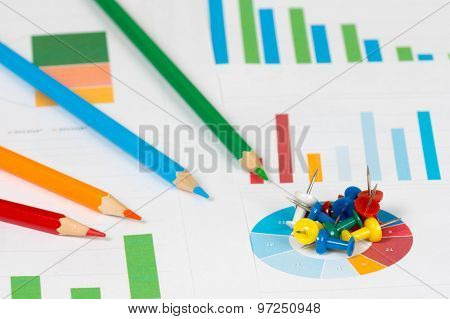Pie And Bar Charts With Pencils And Pins
