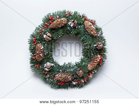 Christmas wreath of fir branches decorated with ilex, cypress cones, pine cones and artificial snow