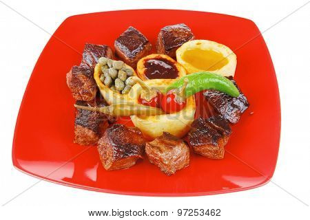 european food: grilled beef meat on red china plate isolated on white background with capers and bbq sauce . shallow dof