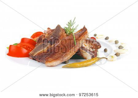 fresh grilled beef meat fillet on white plate with tomatoes and red pepper isolated  over white background
