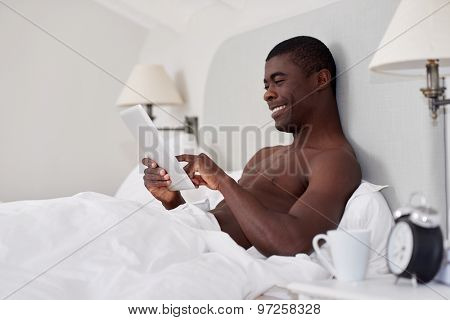 handsome african black man with tablet computer sitting comfortably in bed at home