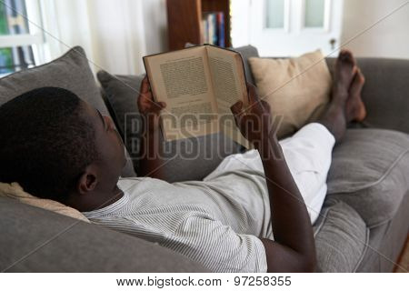 intelligent african black man relaxing on sofa couch reading literature novel story book at home living room lounge