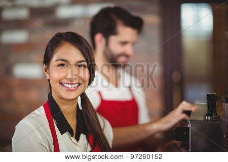 Portrait of a waitress using the coffee machine at the coffee shop