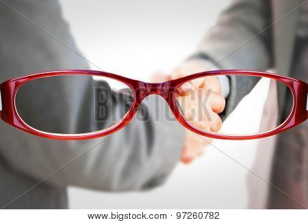 Business people shaking hands close up against glasses