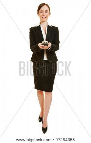 Happy woman working as concierge with hotel bell in her hands