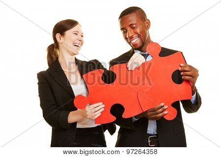 Happy businesspeople solving oversized red jigsaw puzzle together