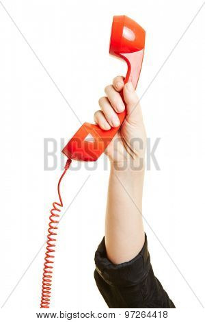 Female hand holding a red phone receiver
